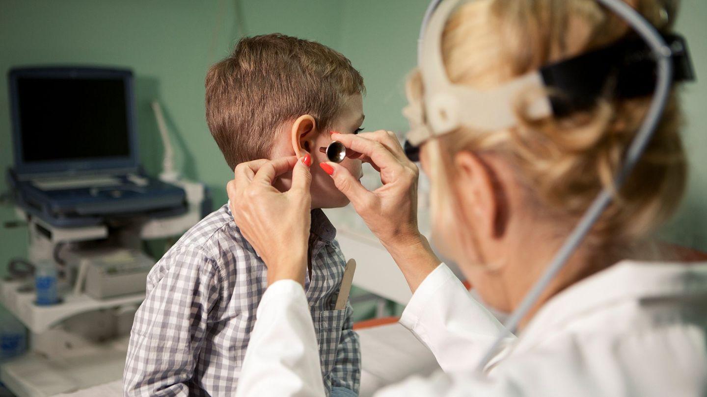 Akute Mittelohrentzündung: Eine Ärztin schaut in das Ohr eines Jungen.