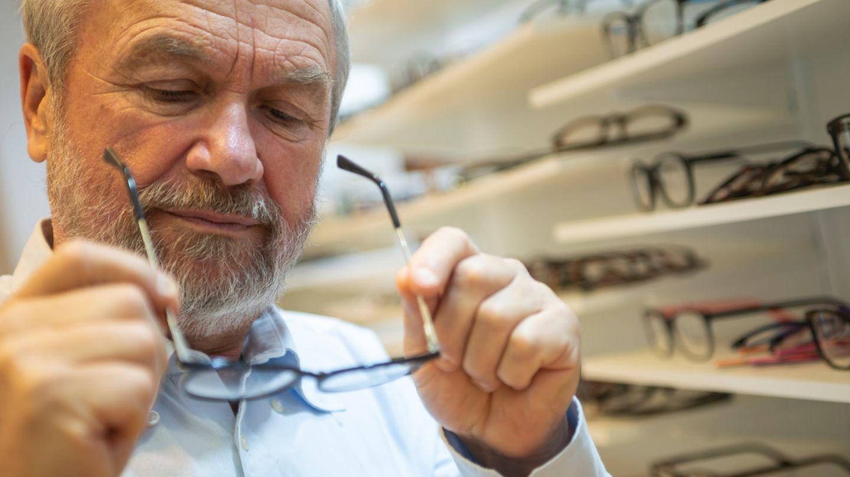 Alterssichtigkeit: Ein älterer Mann begutachtet eine Brille, die er in seinen Händen hält.