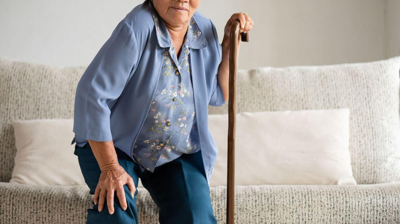 Arthrose: Eine ältere Dame versucht von einem Sofa auzustehen. Sie stützt sich dabei auf einen Gehstock. Sie wirkt angestrengt, eventuell hat sie Schmerzen.
