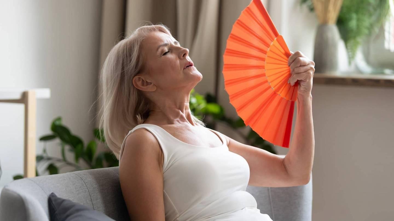 Eine Frau im Top lehnt sich erschöpft zurück und fächert sich mit einem Fächer Luft zu.