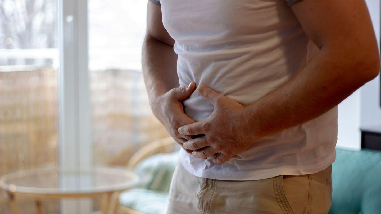 Blinddarmentzündung: Ein Mann steht in seinem Wohnzimmer und hält sich den Bauch. Er wirkt verkrampft und hat scheinbar Schmerzen.