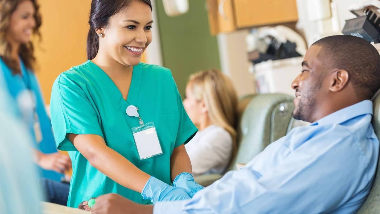 Eine lächelnde medizinische Fachangestellte kümmert sich um einen Blutspender, der auf einem Behandlungstuhl sitzt.