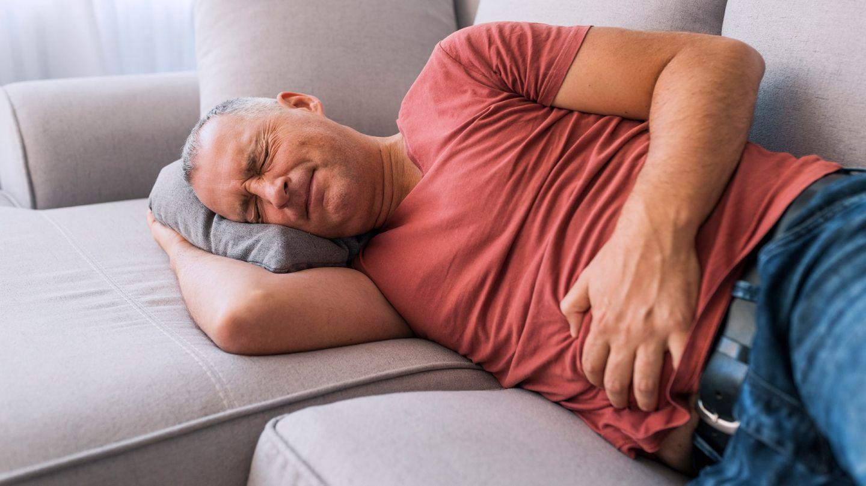 Botulismus: Ein Mann liegt auf einem Sofa und hält sich mit der linken Hand den Bauch. Seine Augen sind geschlossen und sein Gesicht ist schmerzverzerrt.