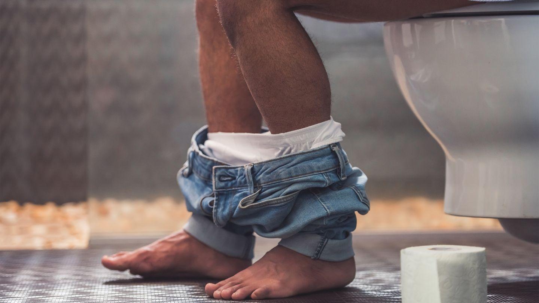 Campylobacteriose: Ein Mann sitzt mit heruntergelassenen Hose auf der Toilette. Zu sehen sind nur seine Beine. Eine Toilettenpapierrolle steht neben seinen Füßen.