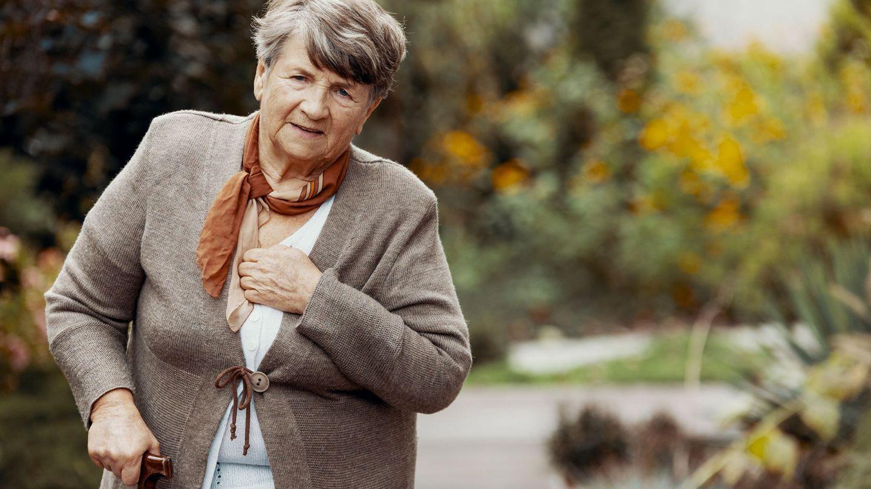 Chronisch-obstruktive Lungenerkrankung: Eine ältere Frau fasst sich an den Brustkorb. In der anderen Hand hält sie einen Gehstock.