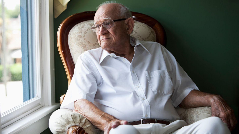 Chronische myeloische Leukämie (CML): Ein älterer Mann sitzt auf einem Sessel und guckt aus dem Fenster. Er wirkt nachdenklich.