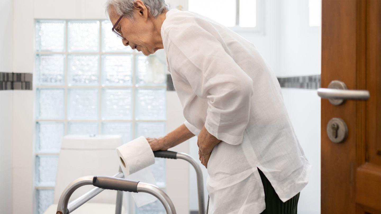 Colitis ulcerosa: Eine ältere Dame ist auf dem Weg zur Toilette. Sie stützt sich auf ihren Rollator und hält sich den Bauch.