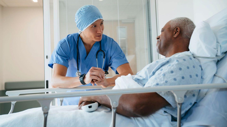Darmkrebs: Ein Arzt steht an einem Krankenbett und beugt sich herunter zu einem Mann, der aufrecht im Bett sitzt. Beide Männer schauen sich an.