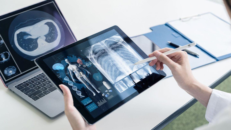 Notfalldatensatz: Eine Person im weißen Kittel hält ein Tablet in einer Hand – in der anderen Hand einen Stift, der auf den Tablet-Bildschirm zeigt. Dort abgebildet ist das 3D-Modell eines menschlichen Körpers sowie das Röntgenbild eines Rumpfes.