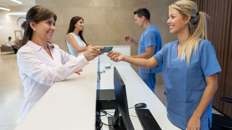 Elektronische Gesundheitskarte: Eine Patientin und eine Sprechstundenhilfe stehen sich am Empfangsbereich einer Praxis an einem Tisch gegenüber. Die Patientin reicht der Sprechstundenhilfe eine Kunststoffkarte.