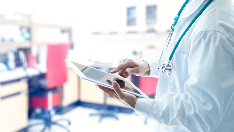 Elektronische Patientenakte: Ein Arzt steht in einer Praxis und hält ein Tablet in der linken Hand. Mit dem Zeigefinger der rechten Hand berührt er den Bildschirm.