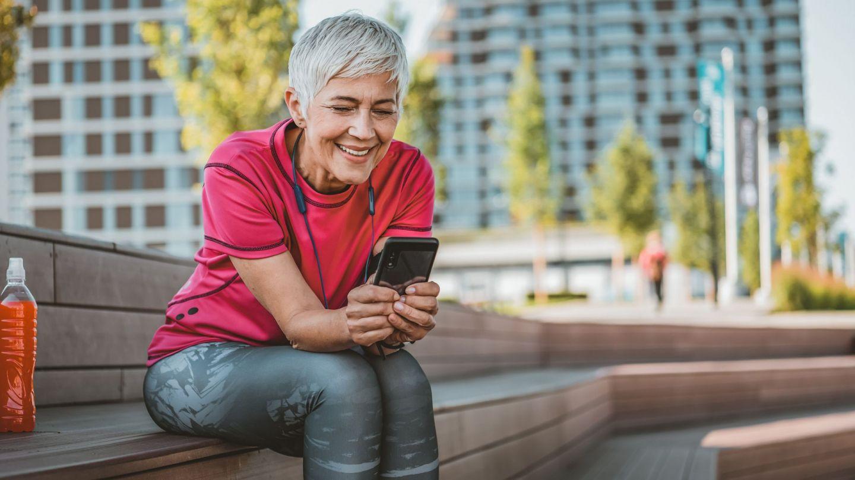 Digitale Gesundheitsanwendungen (DiGA): Eine Frau sitzt auf einer Holzbank und schaut auf den Bildschirm eines Smartphones, das sie in beiden Händen hält.