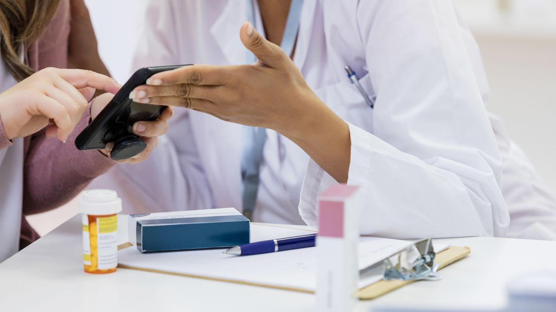 E-Arbeitsunfähigkeitsbescheinigung: Eine Patientin schaut gemeinsam mit einer Ärztin auf ihr Handy. Vor ihnen auf dem Tisch liegen einige Medikamente.