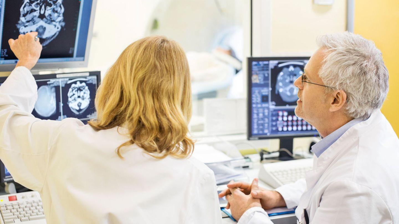 Epilepsie: Eine Ärztin und ein Arzt begutachten das gescannte Bild eines Schädels und Gehirns auf einem Monitor.