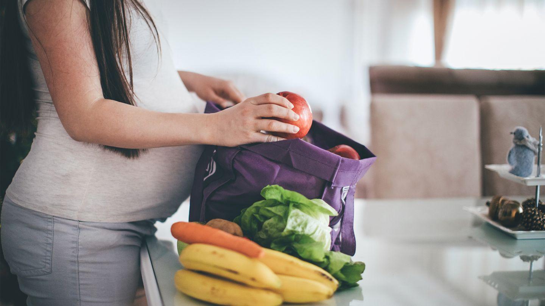 Eine schwangere Frau steht in der Küche und packt ihren Einkauf aus. Sie hat viel unverpacktes frisches Obst und Gemüse gekauft.