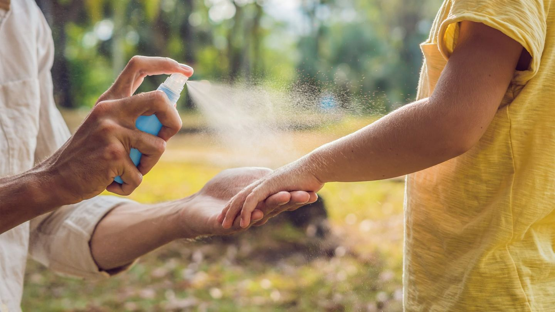 Exotische Infektionskrankheiten: Nahaufnahme von Händen und Armen zweier T-Shirt tragender Personen vor einem parkähnlichem Hintergrund. Eine Person hält den Arm der anderen und sprüht Mückenschutz darauf.