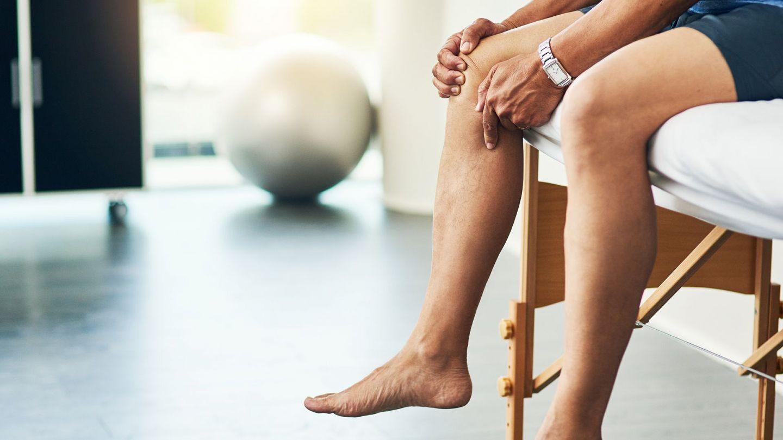 Funktionelle Beschwerden: Ein Mann sitzt auf einem Stuhl in einem Praxiszimmer und greift sich ans Knie.