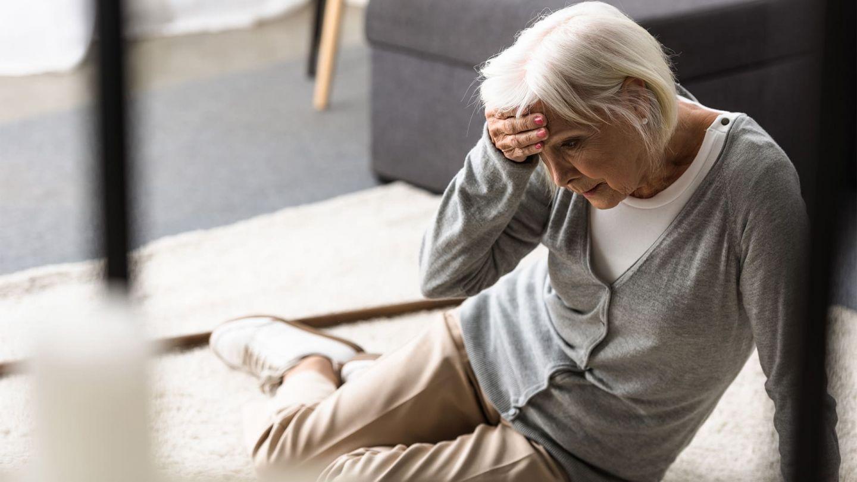 Gehirnerschütterung: Eine ältere Frau sitzt auf dem Wohnzimmerboden. Sie stützt sich mit einem Arm auf dem Boden ab, die andere Hand hält den Kopf. Sie wirkt benommen und ihr Blick geht zum Boden.