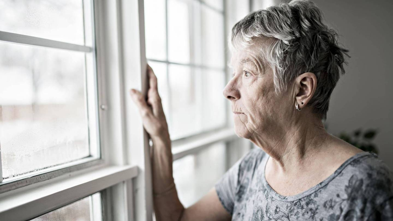 Eine ältere Frau lehnt am Fenster und schaut betrübt nach draußen.