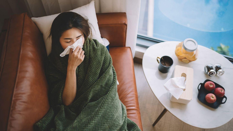 Grippe: Eine junge Frau sitzt in einem Sessel. Ihr Oberkörper ist bis unters Kinn mit einer Decke eingehüllt. Mit einer Hand hält die Frau ein Taschentuch an ihre Nase.