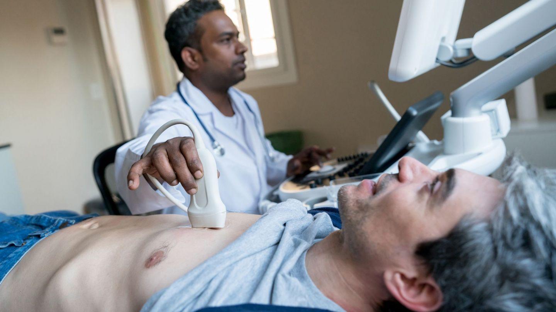 Herzklappenerkrankung: Ein Mann mittleren Alters liegt mit dem Rücken auf einer Behandlungsliege. Neben ihm steht ein Arzt. Mit einer Hand hält er ein Messgerät auf das Brustbein des Patienten. Der Arzt untersucht ihn per Ultraschall.