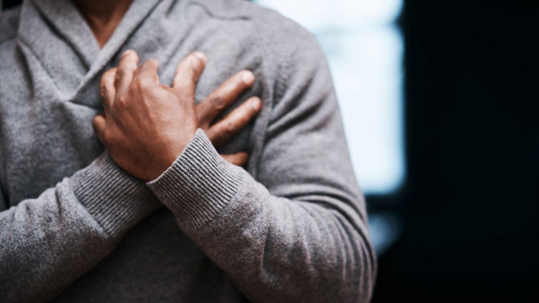 Herzrasen: Ein Mann fasst sich mit beiden Händen an sein Herz.