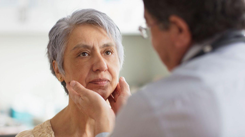 Hodgkin-Lymphom: Eine Frau wird von einem Arzt am oberen Hals unter dem Kinn abgetastet.