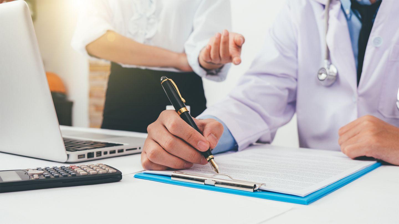 IGeL-Leistungen: Ein Arzt sitzt am Schreibtisch und füllt ein Formular aus. Eine Frau mit weißer Bluse steht hinter ihm. Sie hat den rechten Arm vor dem Bauch verschränkt und mit dem anderen Arm macht sie eine Handbewegung in Richtung des Arztes.
