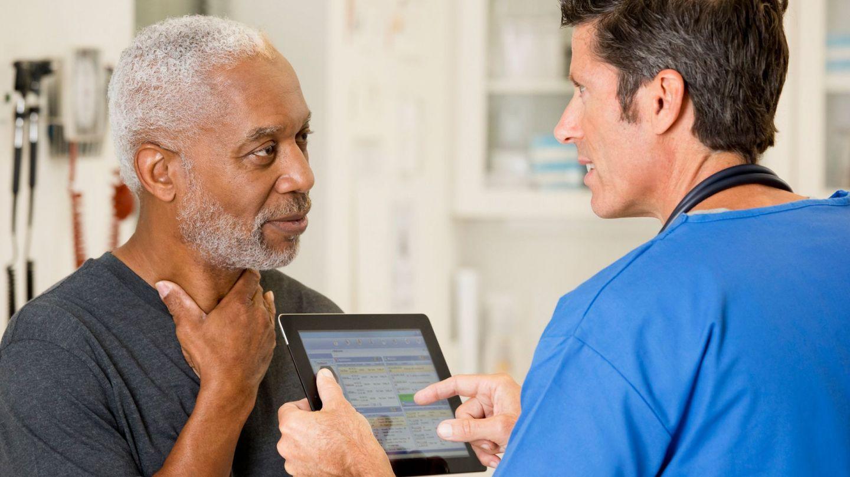 Kehlkopfkrebs: Ein älterer Mann fasst sich mit der linken Hand an den Hals. Ihm gegenüber steht ein Arzt, der ein Tablet in beiden Händen hält.