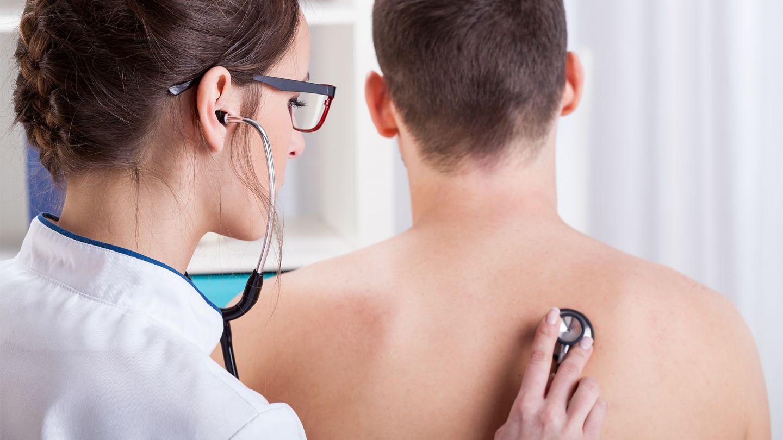 Lungenentzündung: Eine Ärztin hält ein Stethoskop an den nackten Rücken eines Mannes.