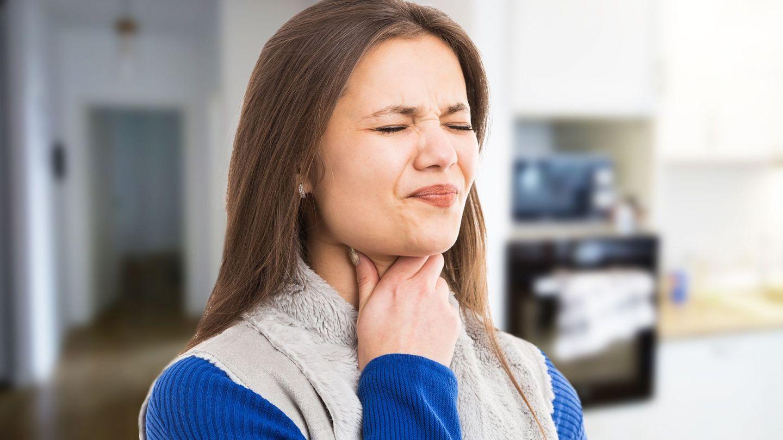 Mandelentzündung: Eine Frau fasst sich an den Hals, verzieht ihr Gesicht und kneift die Augen zusammen.