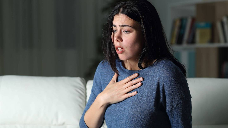 Eine Frau hält ihre flache Hand auf der Brust, sie ist verkrampft und unter akuter Atemnot.