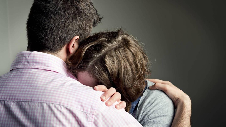Eine Frau lehnt sich mit dem Kopf an die Schulter eines Mannes. Sie versteckt dabei ihr Gesicht an seiner Brust. Sie wirkt verzweifelt.