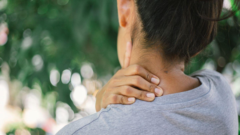 Nackenschmerzen: Eine Frau massiert sich ihren Nacken mit der linken Hand.