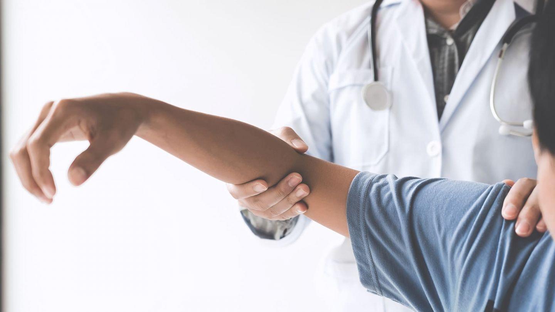Neuralgische Amyotrophie: Eine Person mit Arztkittel und umgehängtem Stethoskop untersucht den Arm eines Patienten, indem sie Schulter und Ellbeuge fasst und augenscheinlich leicht bewegt.