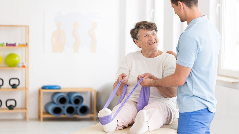 Osteoporose: Eine ältere Fau sitzt mit augestreckten Beinen auf einer Isomatte. Um einen Fuß hat die Seniorin ein Fitnessband gespannt, an dem sie mit beiden Händen zieht. Ein Trainer steht neben der Frau und stützt sie am Rücken und an einer Hand.