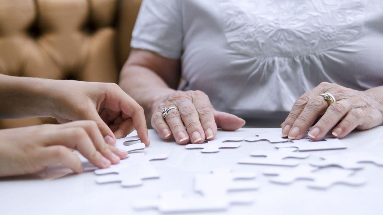 Häusliche Pflege von Angehörigen mit Demenz: Die Hände einer älteren Frau und einer jüngeren Person berühren große Puzzleteile, die auf einer Tischplatte ausgebreitet sind.
