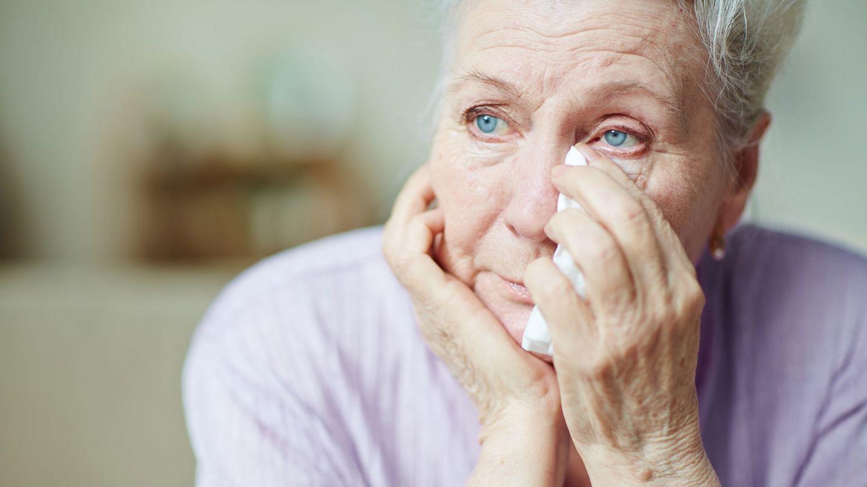 Psychische Gesundheit im Alter: Eine ältere Frau guckt nachdenklich geradeaus. Ihren Kopf hat sie auf eine Hand gestützt, mit der anderen Hand hält sie ein Taschentuch an ihr Gesicht. Sie wirkt traurig.