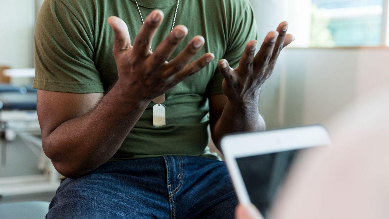 Ein Mann sitzt im Sprechzimmer einer Praxis vor einem Psychotherapeuten.