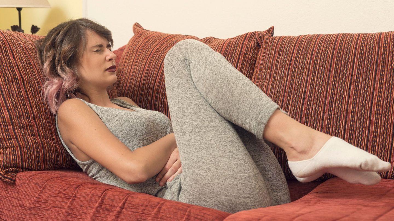 Regelschmerzen: Eine Frau liegt mit dem Rücken auf einer Couch, hat ihre Beine in Richtung Oberkörper angewinkelt und hält sich mit beiden Händen den Bauch. Sie presst leicht ihre Lippen zusammen.