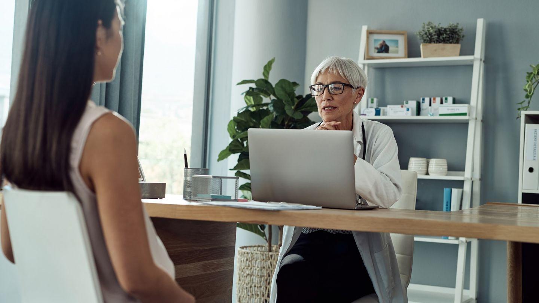Scheidenpilz: Eine Frau sitzt in einem Behandlungszimmer. Ihr gegenüber sitzt eine Ärztin und guckt auf ihren Laptop.