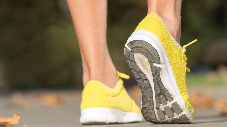 Sprunggelenkverstauchung: Ein Jogger steht mit beiden Beinen auf einer asphaltierten Lauffläche. Das rechte Bein zieht der Sportler an der Ferse etwas nach oben an, sodass er bei einem Bein nur auf dem Fußballen steht.