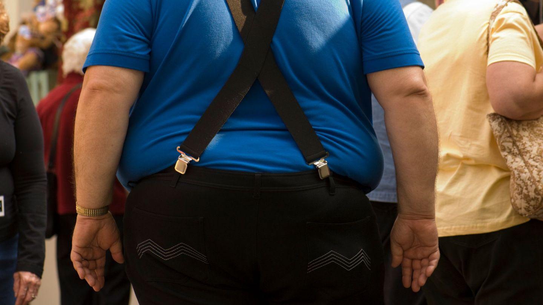 Übergewicht und Adipositas: Ein Mann, der Latzhose trägt, steht in einer Menschenmenge. Links und rechts am Hosenbund drückt der Bauch über den Hosenrand.