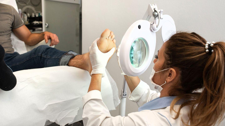 Warzen: Ein Mann sitzt auf einem Behandlungsstuhl in einer Praxis und streckt ein Bein nach vorne. Eine junge Frau, die einen weißen Kittel, Mundschutz und Medizinhandschuhe trägt, hält einen Fuß des Mannes fest und trägt Stickstoff auf eine Stelle auf.