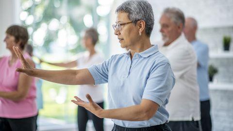 Abwehrkräfte: Mehrere Menschen stehen in einem hellen Raum und führen Bewegungsübungen durch. Im Vordergrund steht eine ältere Frau die mit beiden Armen eine Bewegung ausführt.
