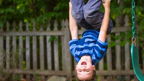 Ein lachender Junge hält sich kopfüber mit beiden Händen an einem Spielgerüst fest und klammert sich auch mit den Füßen daran.