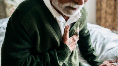 Angina Pectoris: Ein alter Mann sitzt müde auf einem Bett und fasst sich an den Brustkorb.