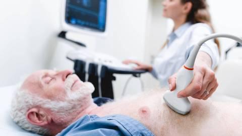 Ein älterer Mann liegt mit geschlossenen Augen auf einer Liege. Im Hintergrund ist eine Ärztin zu sehen. Sie untersucht das Herz des Mannes per Ultraschall.