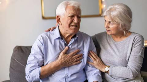 Ein älterer Herr sitzt auf dem Sofa und hat seine Hand mit schmerzverzerrtem Gesicht auf seine Brust gelegt. Eine ältere Dame sitzt neben ihm, legt ihm fürsorglich ihre Hände auf Schulter und Arm und sieht ihn besorgt an.