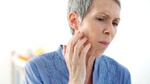 Aphthen: Eine Frau fasst sich mit einer Hand an die rechte Wange und verzieht ihr Gesicht. Der Mund ist dabei geschlossen..